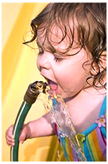 child drinking water from a hose